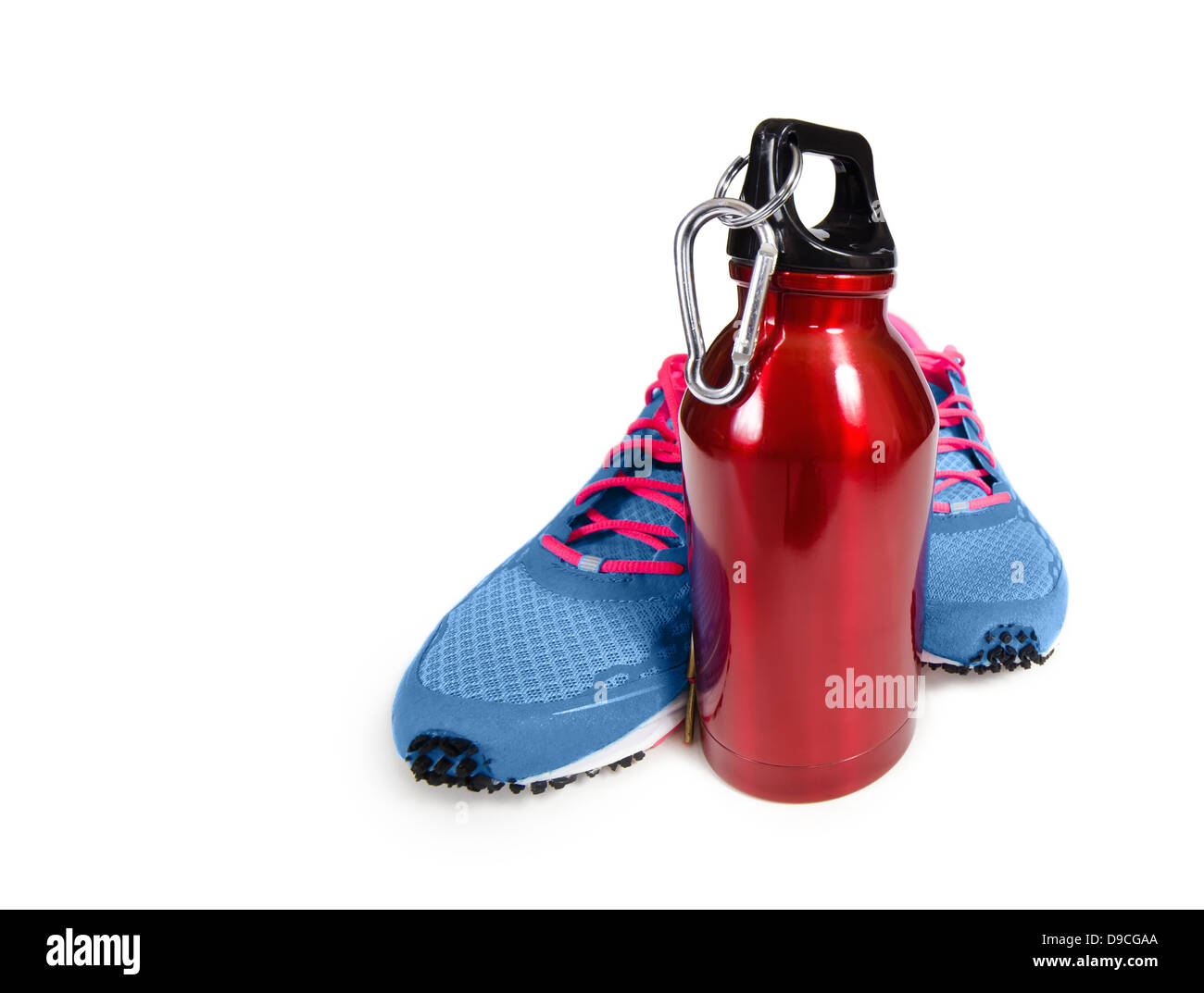 Red stainless steel water bottle with running shoes over white. Exercise and hydration concept. Stock Photo