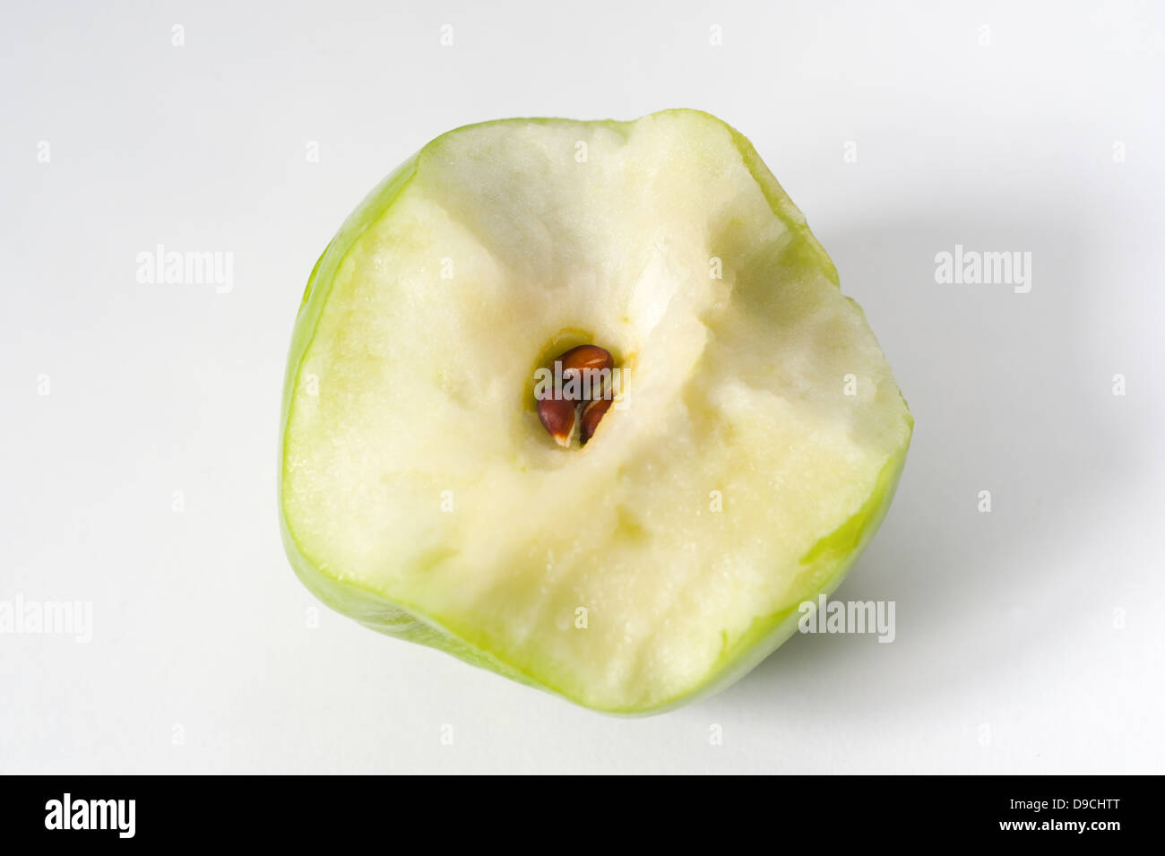 A half eaten green apple showing the core and seeds - Stock Image