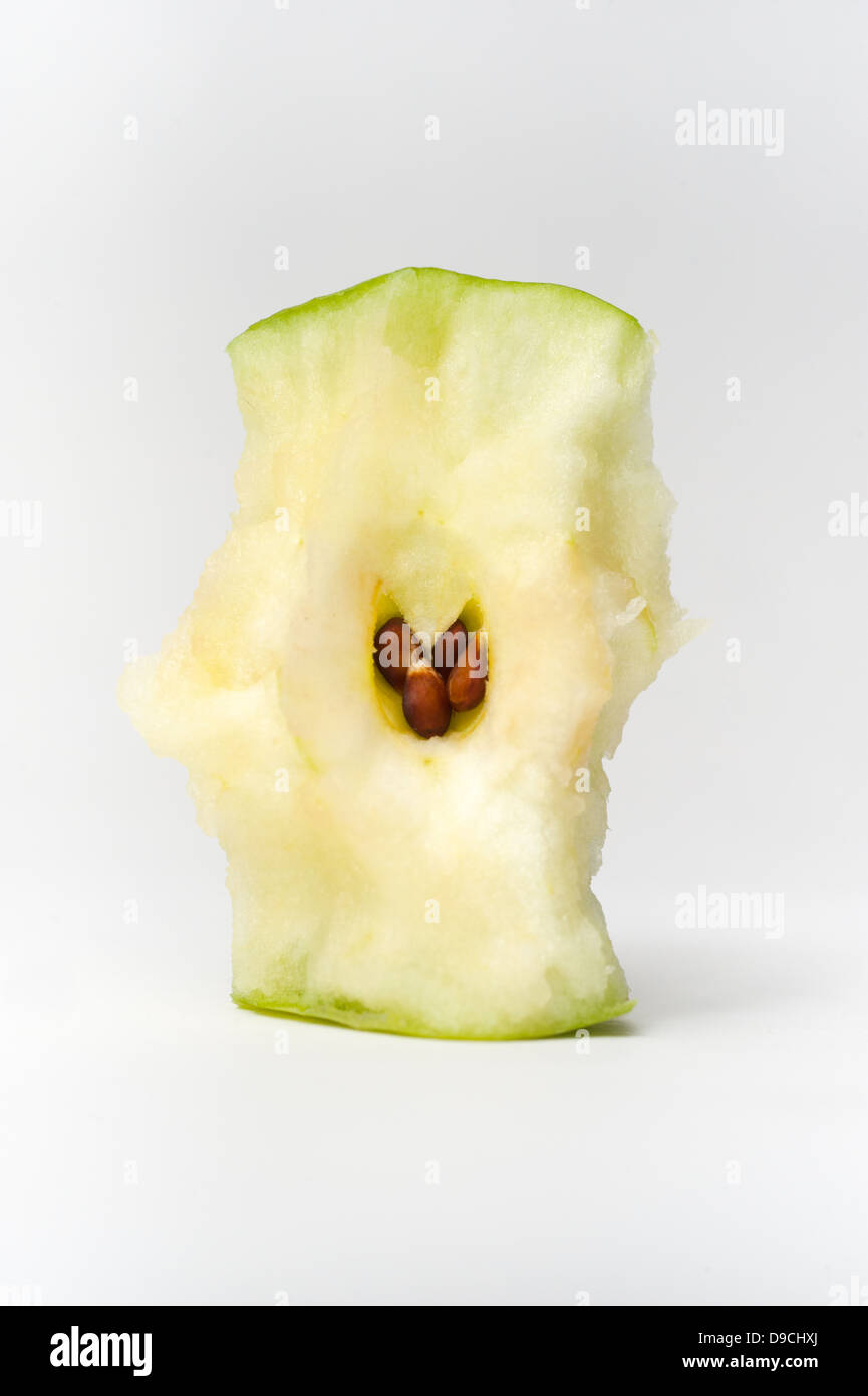 A green apple core showing the seeds - Stock Image