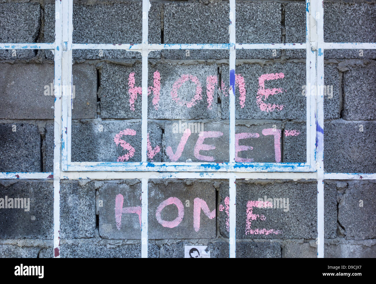 Home sweet home painted on bricked up building - Stock Image