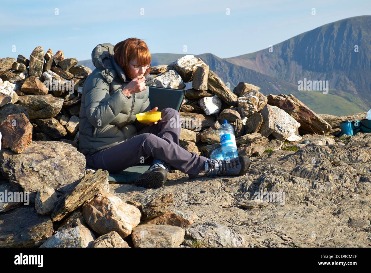 A hiker eating breakfast in the morning sun after camping on the summit of Robinson in the Lake District - Stock Image