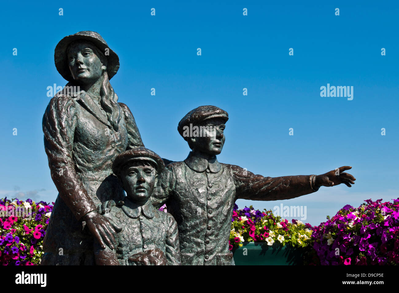 The Annie Moore Memorial, statue of Annie Moore and her two Brothers in Cobh, Ireland - Stock Image