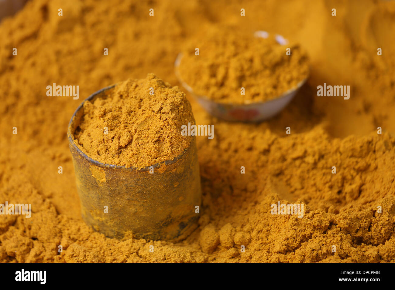 tin cup of ground tumeric spice on mound of tumeric in market on Inle Lake, Myanmar, Southeast Asia - Stock Image