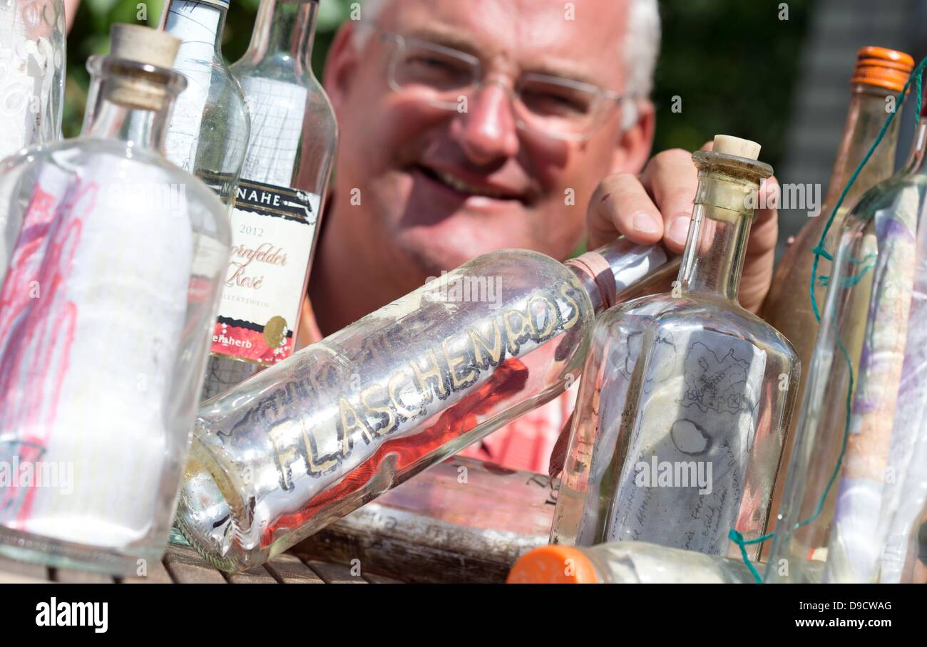 Frank Beerens smiles as he looks at a drift bottle in Meppen, Germany, 5 June 2013.  Beerens collects drift bottles - Stock Image