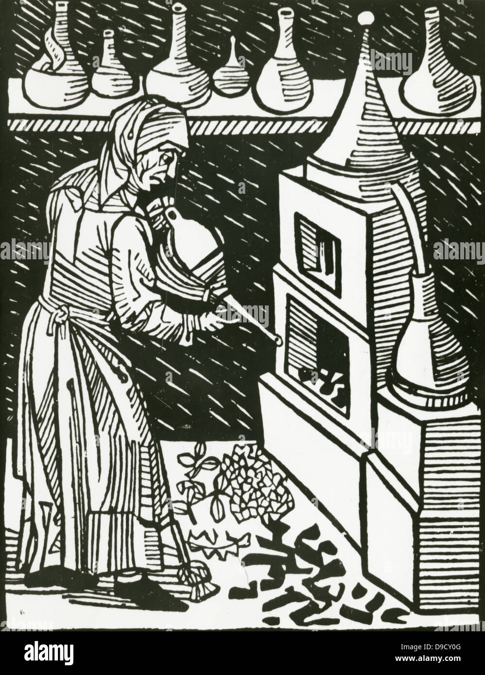 Female operator applying bellows to the furnace during distillation.  Woodcut, 1514. - Stock Image