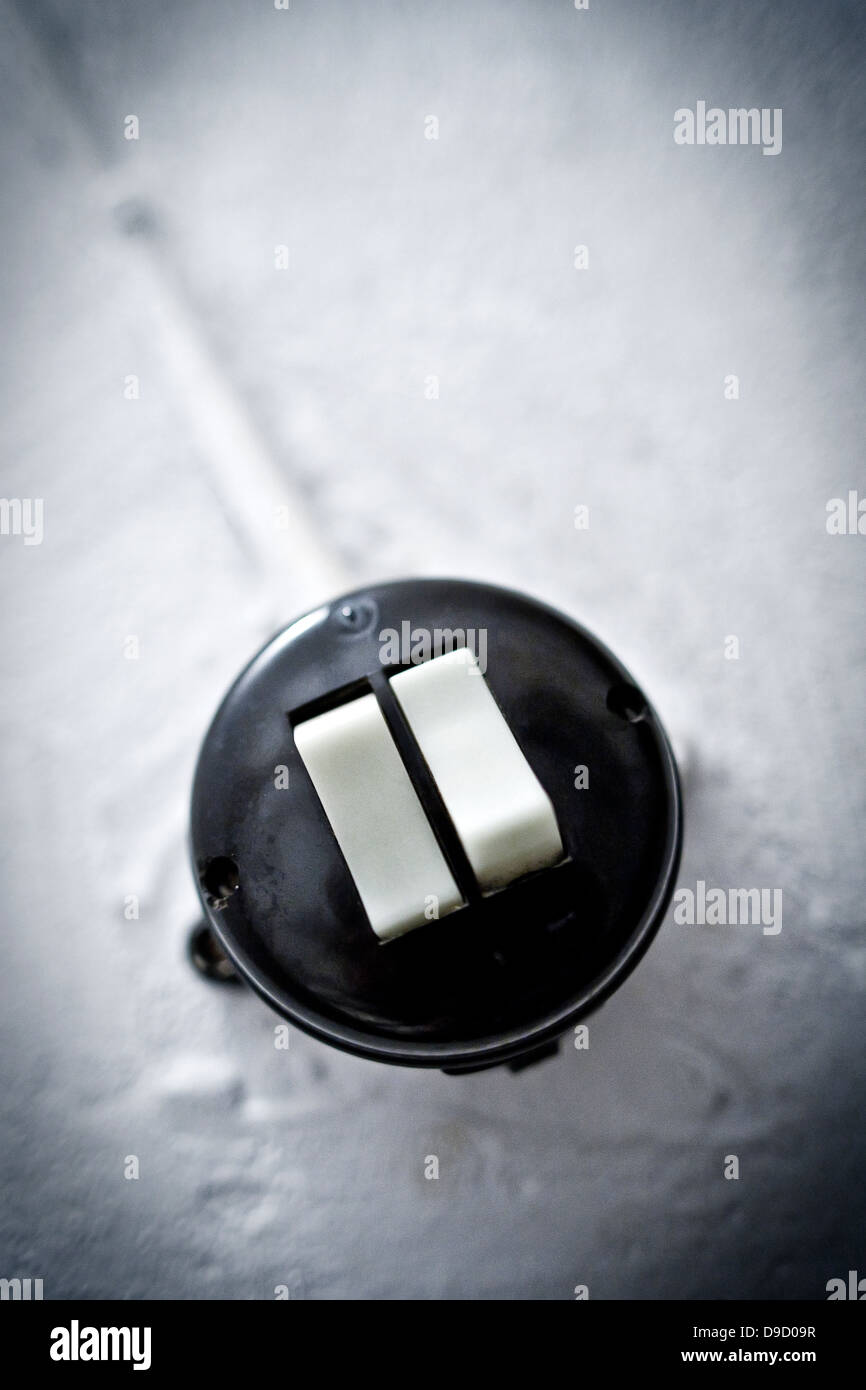 Old light switch in a cellar rising, Old light switch in a basement stairway - Stock Image