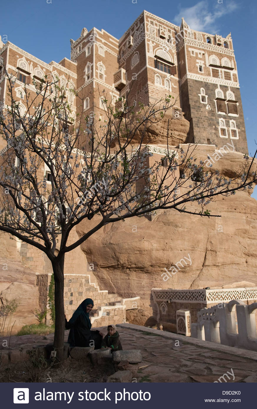 Woman sitting near a tree with a palace in the background, Dar Al-Hajar, Wadi Dhar, Sana'a, Yemen - Stock Image