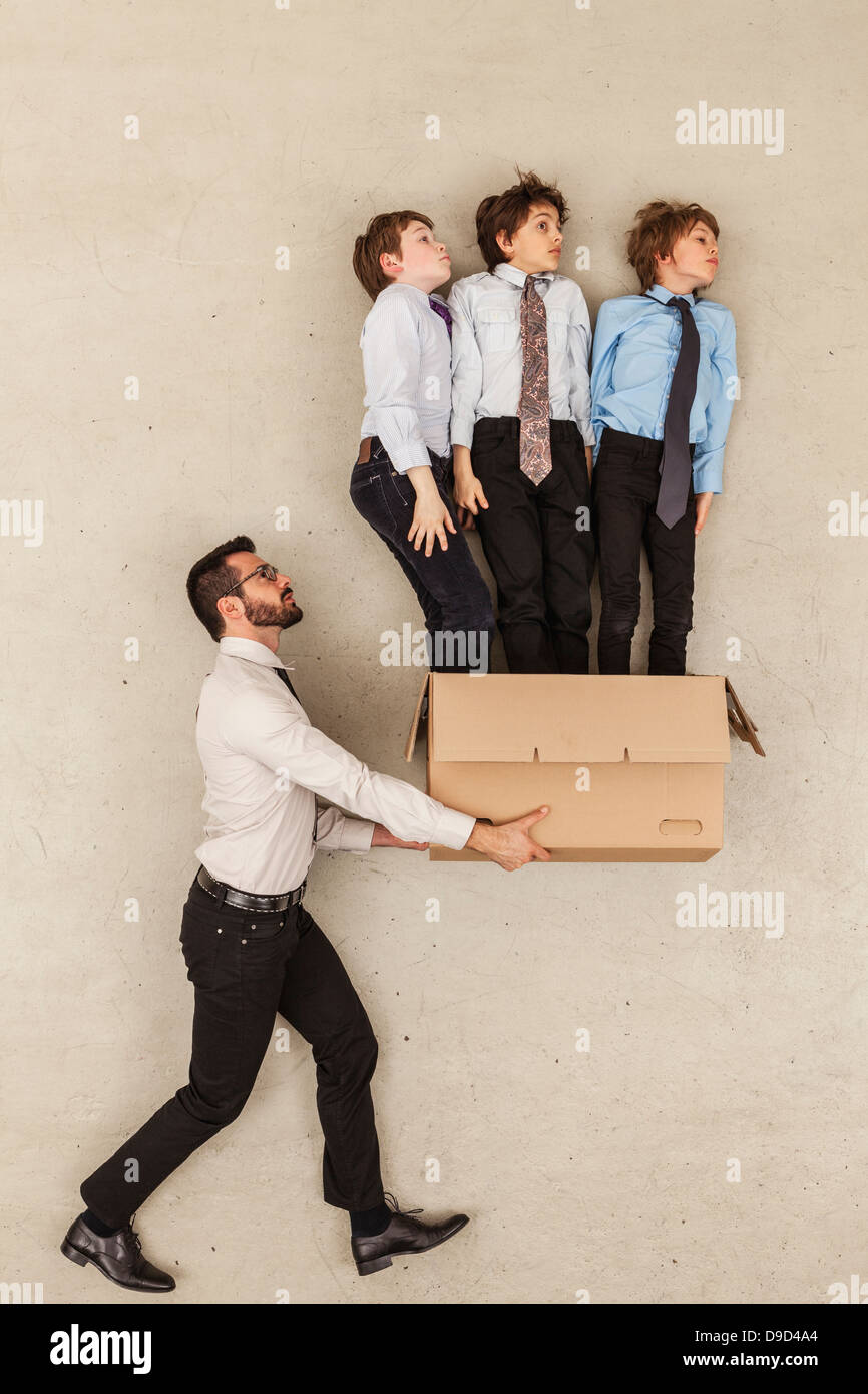 Businessman holding cardboard box while boys flying out - Stock Image