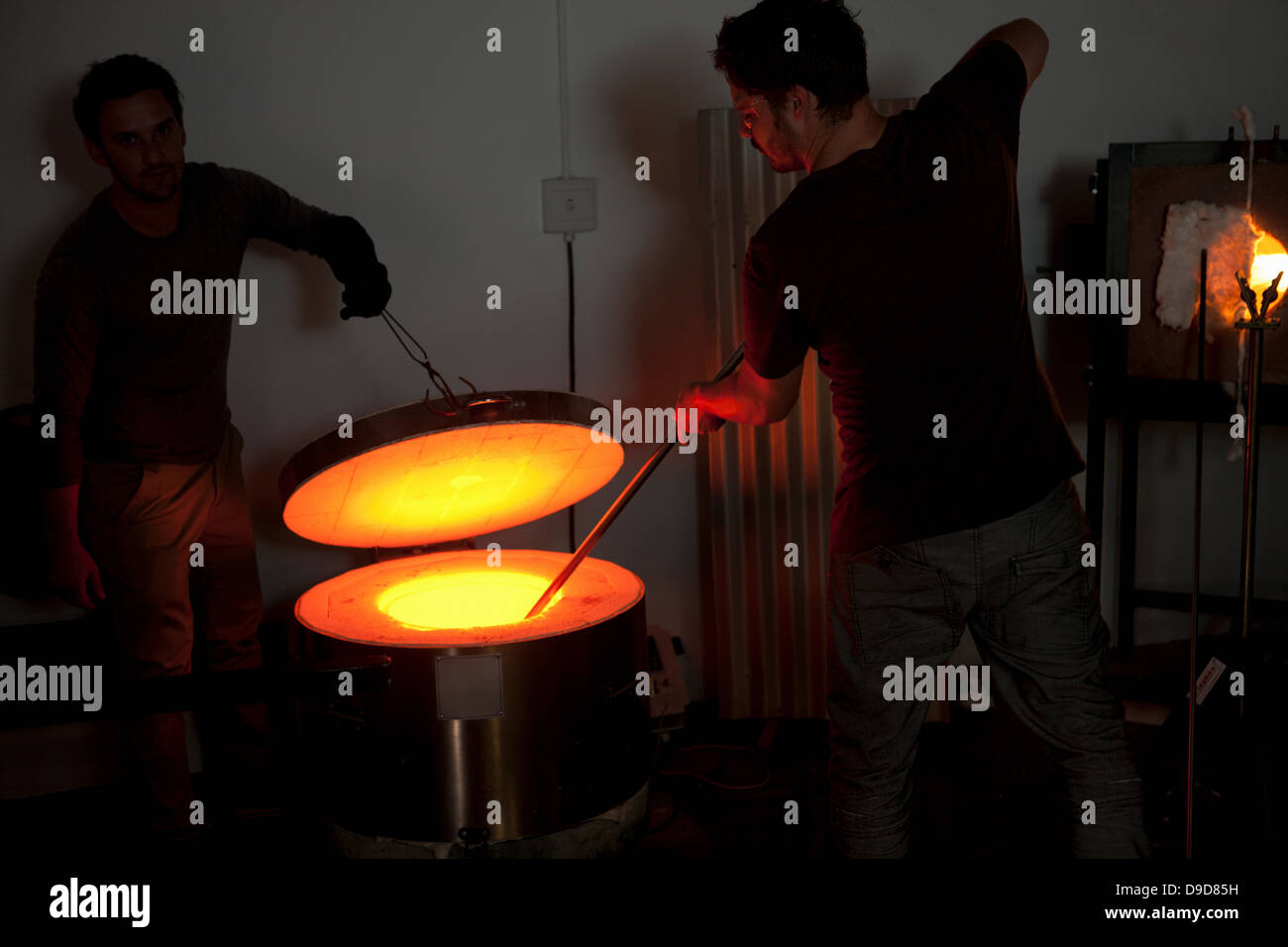 Two men working in glass factory - Stock Image