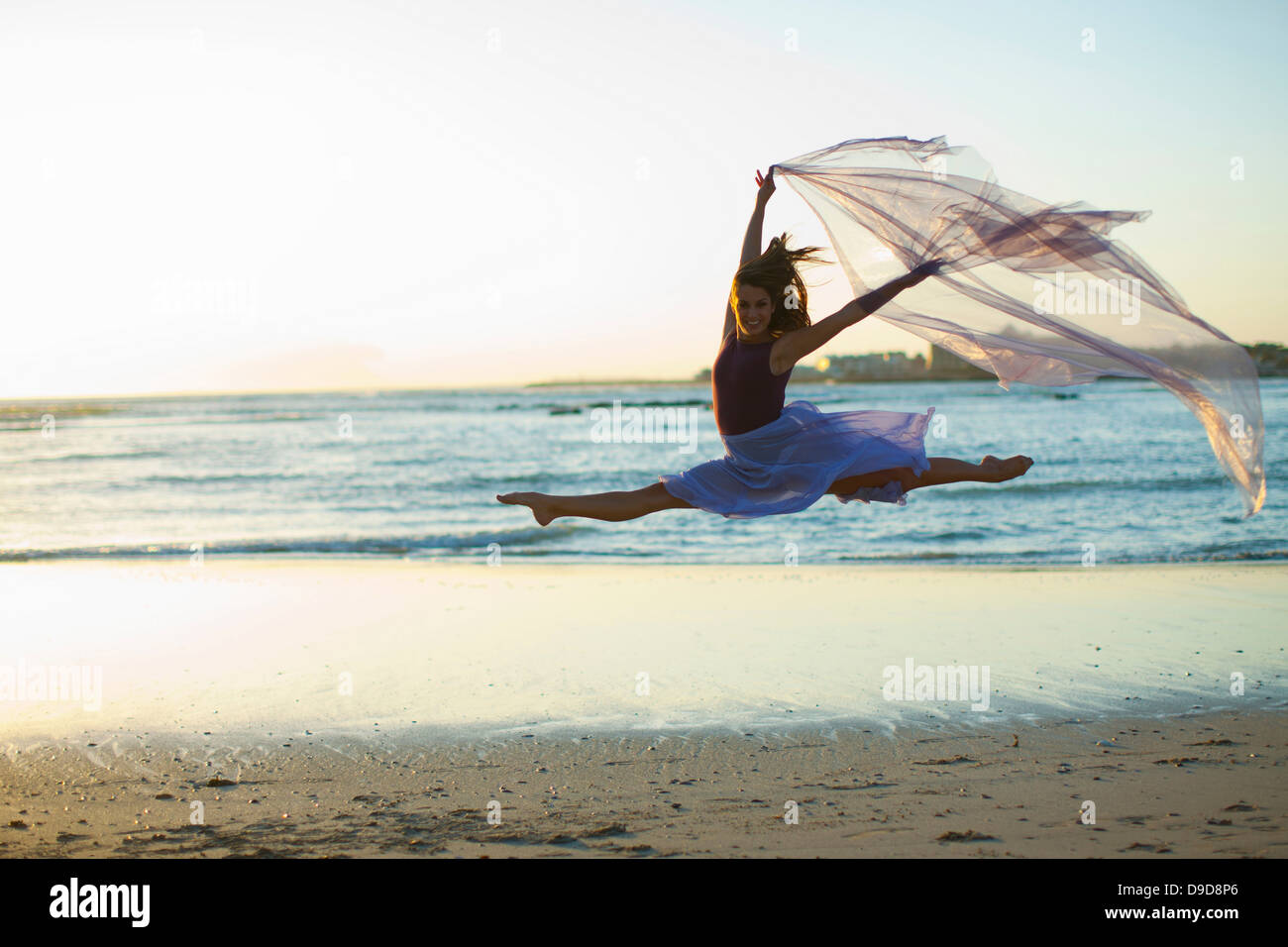Young woman dancing on sunlit beach - Stock Image