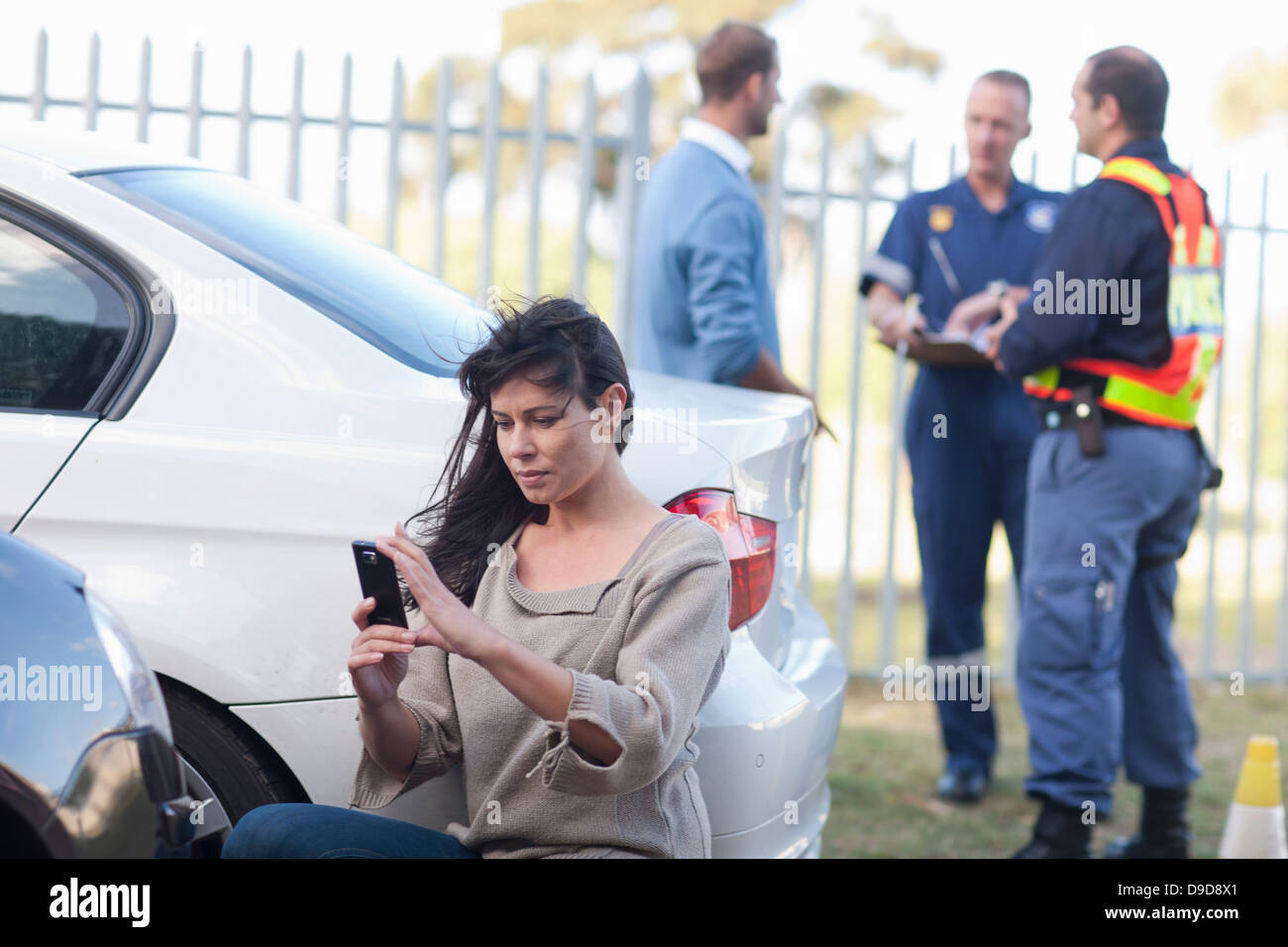 Woman photographing damage on her car at car accident scene - Stock Image