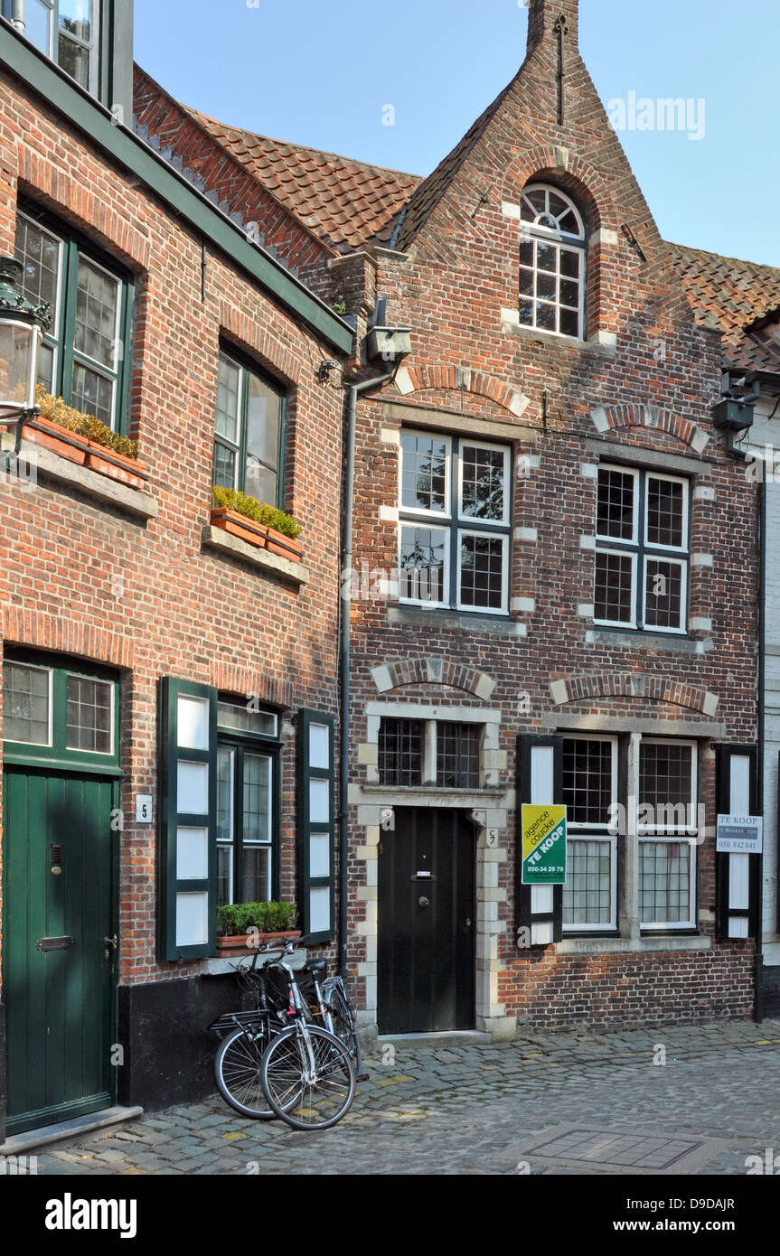 A house for sale in a side street in Bruges, Belgium, Europe. Familar bicycles in view. Stock Photo