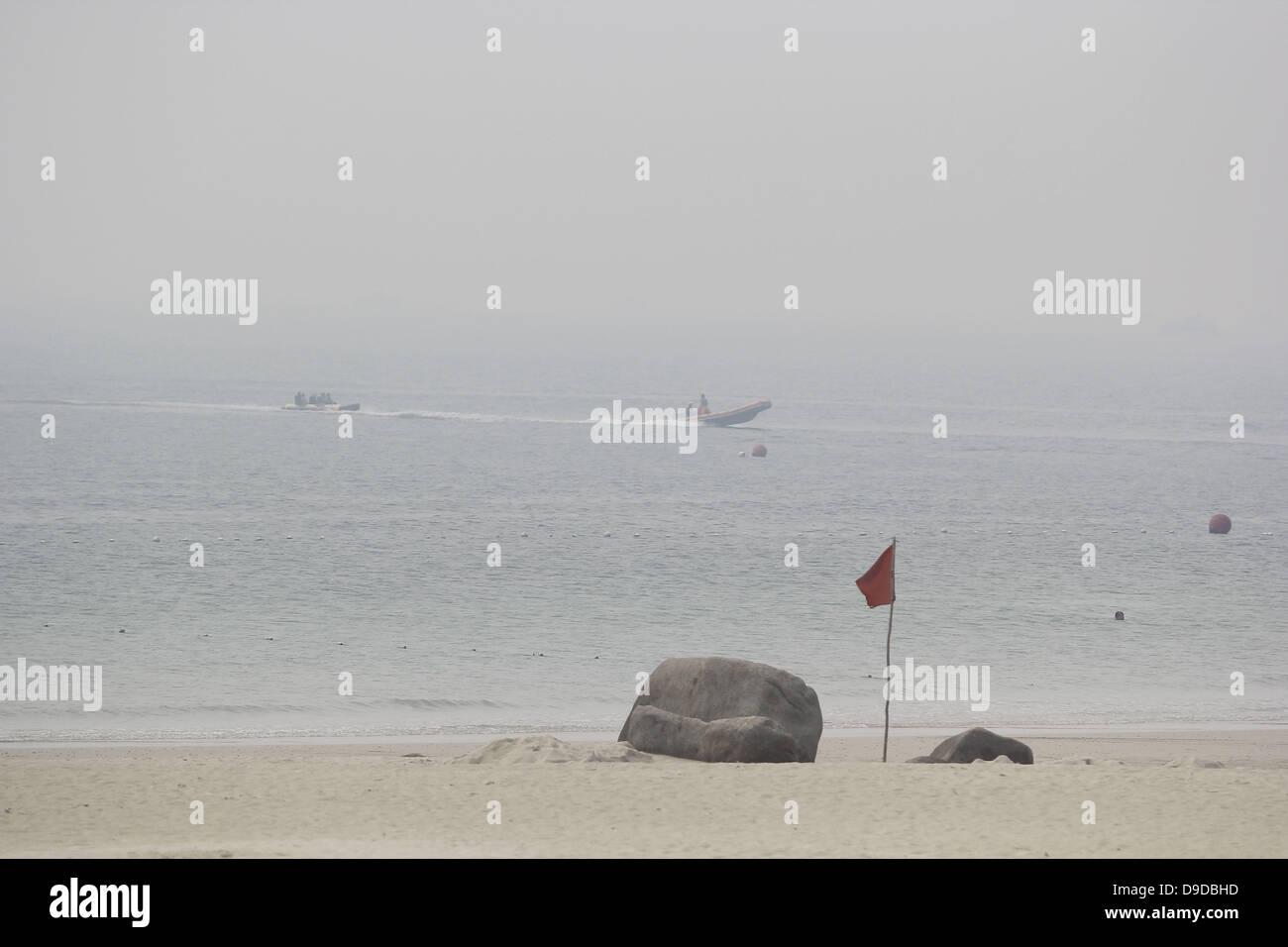Bintan Island, Indonesia. 17th June, 2013. JUNE 17, 2013:Tourists are playing on the Bintan Lagoon beach with haze - Stock Image