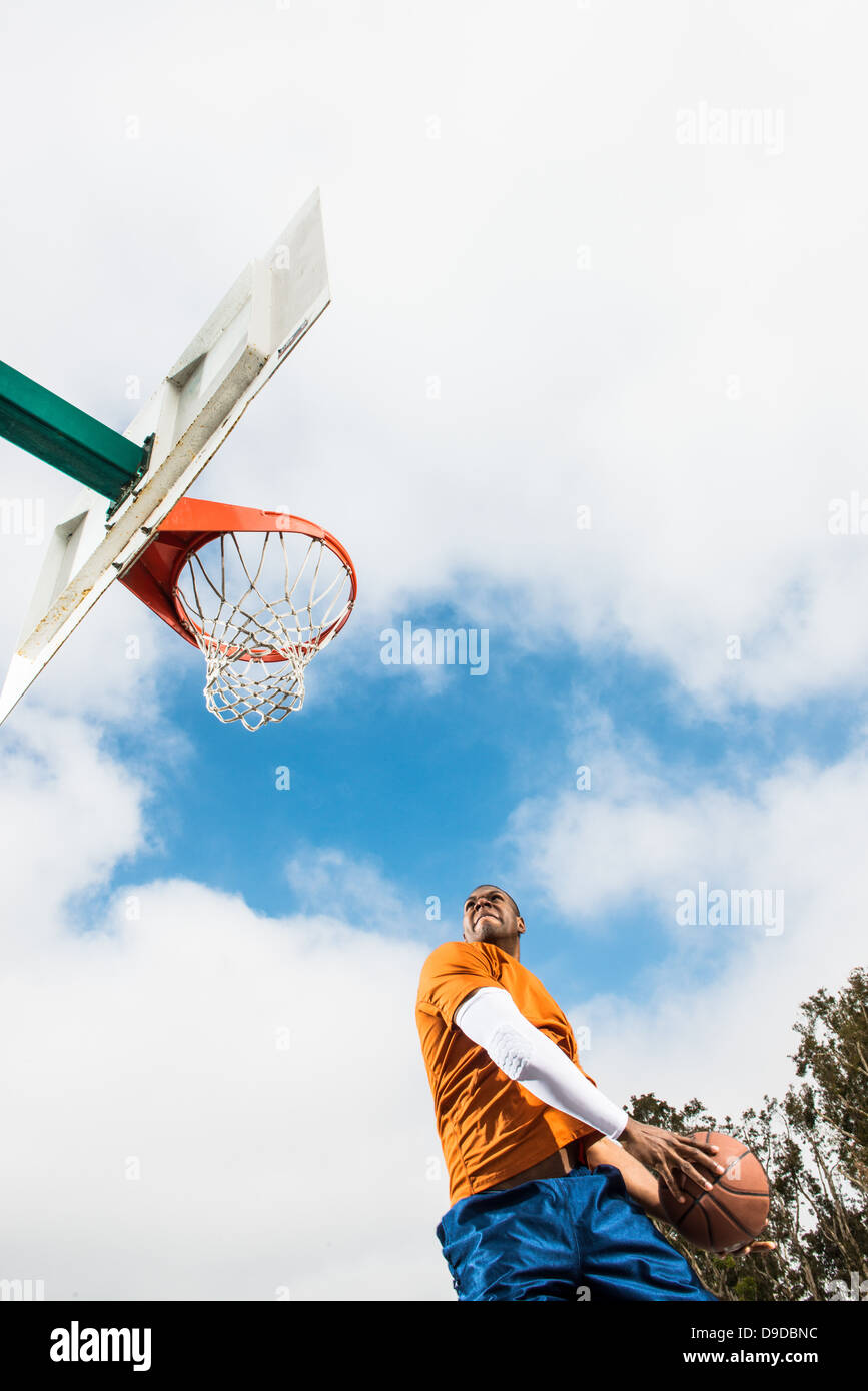 Young man jumping to score hoop in basketball - Stock Image