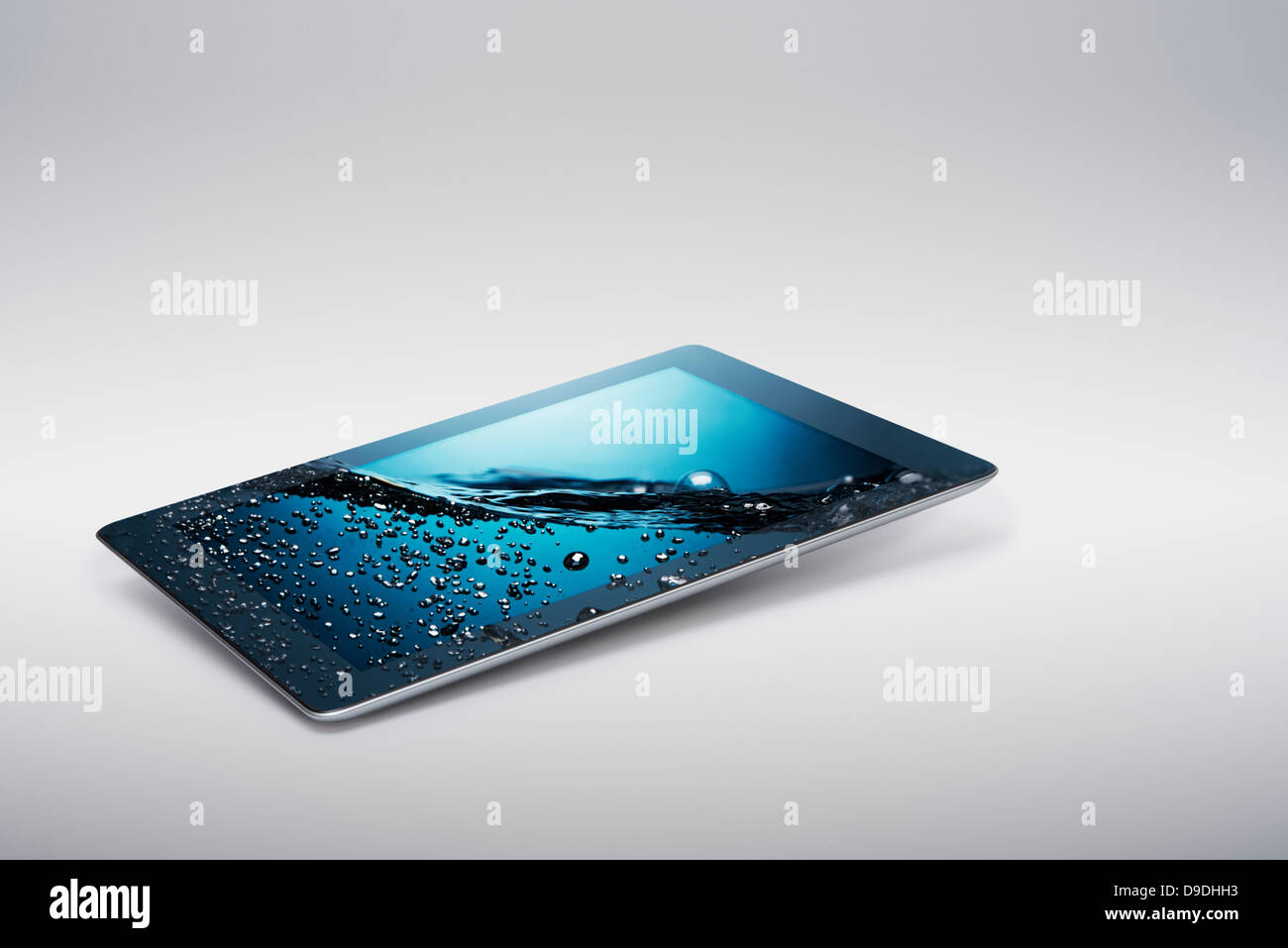 Digital tablet with gently rising bubbling water on screen - Stock Image