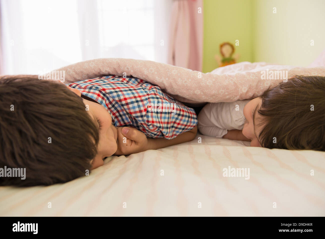 Brother and sister lying on bed - Stock Image