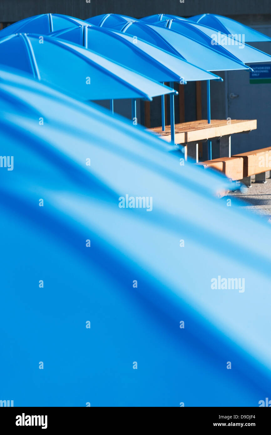 Picnic tables with blue umbrellas - Stock Image