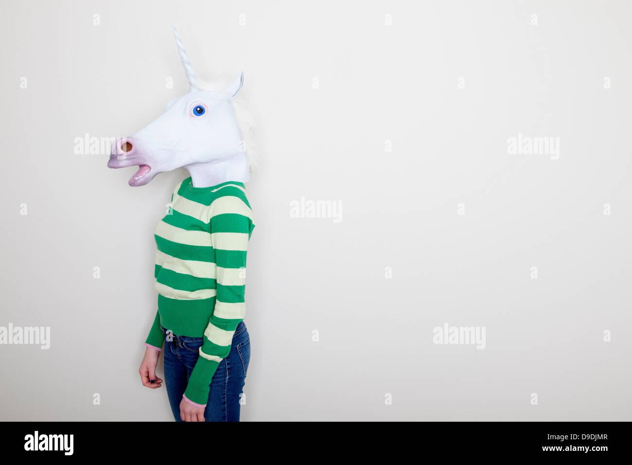 Girl wearing unicorn head - Stock Image
