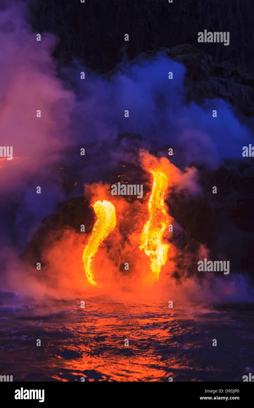 Lava flow impacting sea at dusk, Kilauea volcano, Hawaii - Stock Image