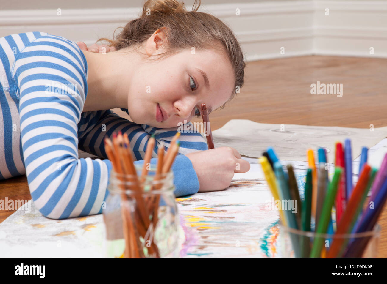 Girl lying on floor drawing picture - Stock Image