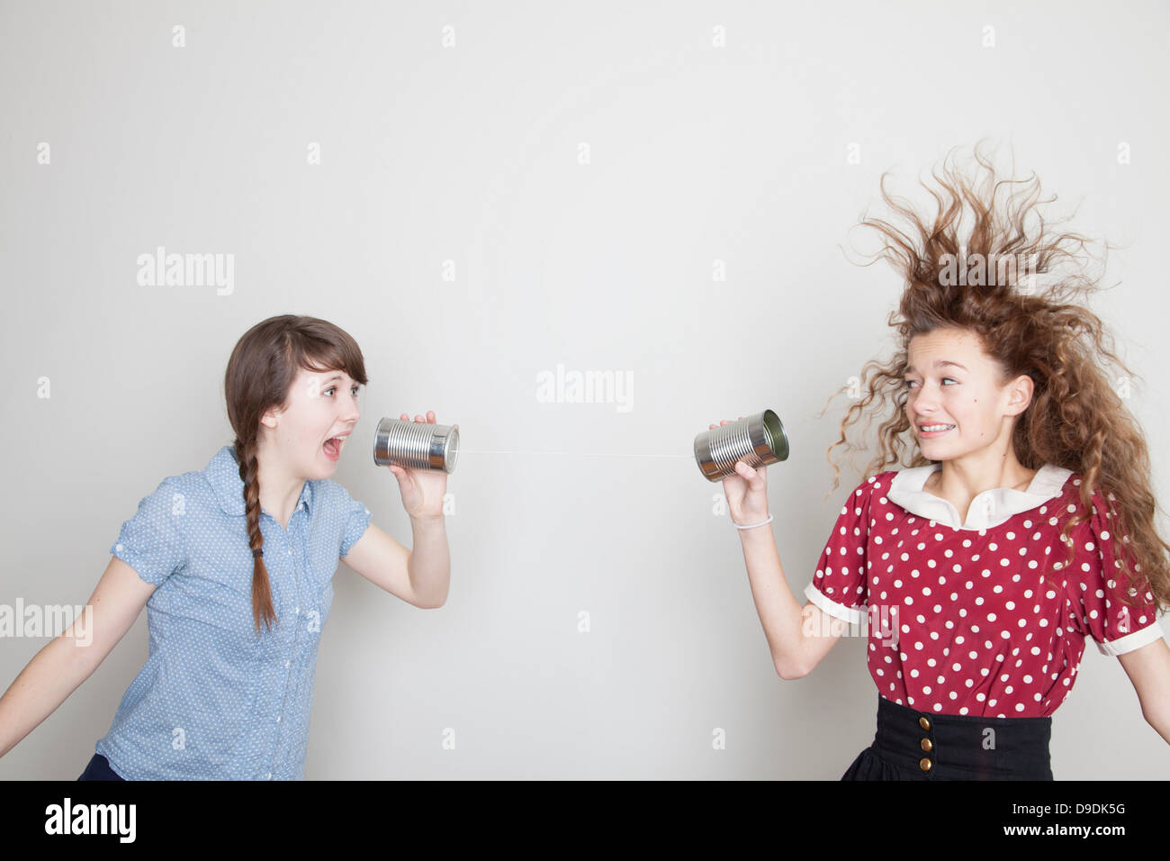 Girls using tin can telephones - Stock Image
