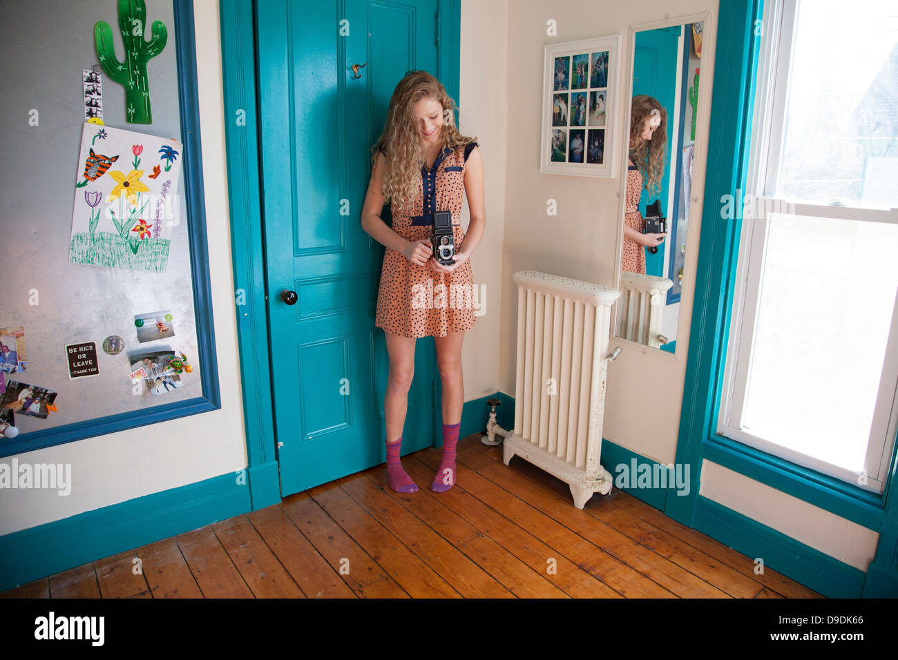 Teenager standing in bedroom with antique camera - Stock Image
