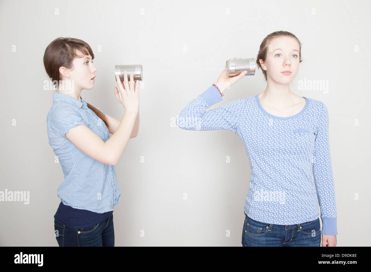 Two girls with tin cans - Stock Image