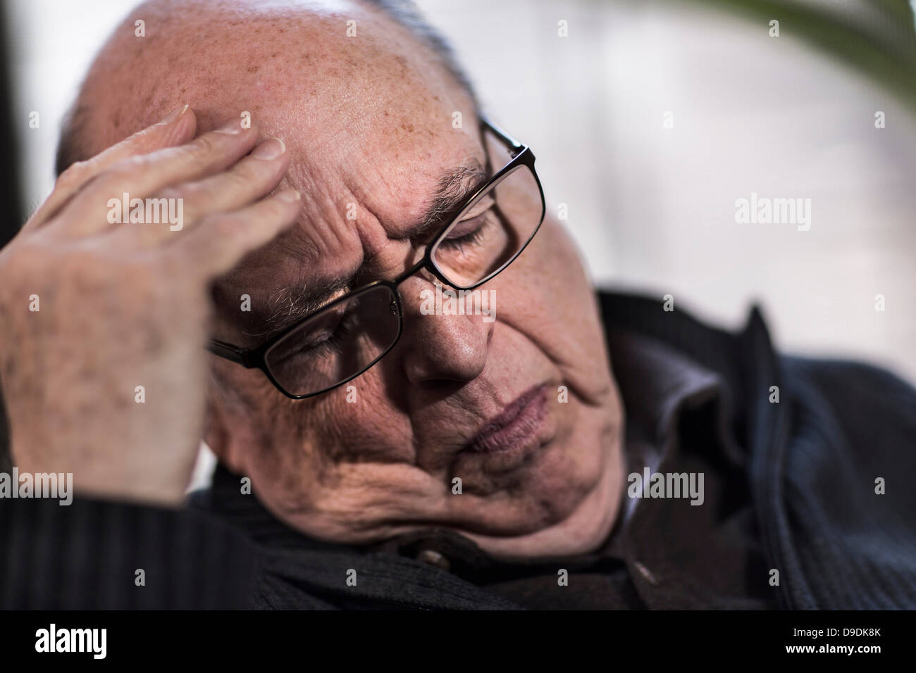 Senior man with eyes closed, wearing glasses, looking stressed - Stock Image