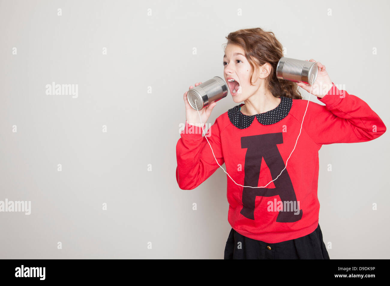 Girl shouting into tin can telephone - Stock Image