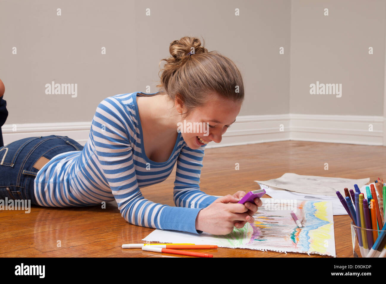Girl lying on floor with smartphone and art materials - Stock Image
