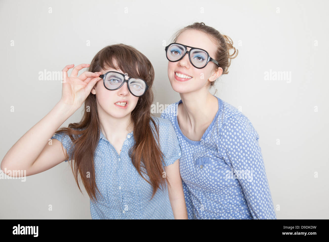 Two girls wearing fake glasses - Stock Image