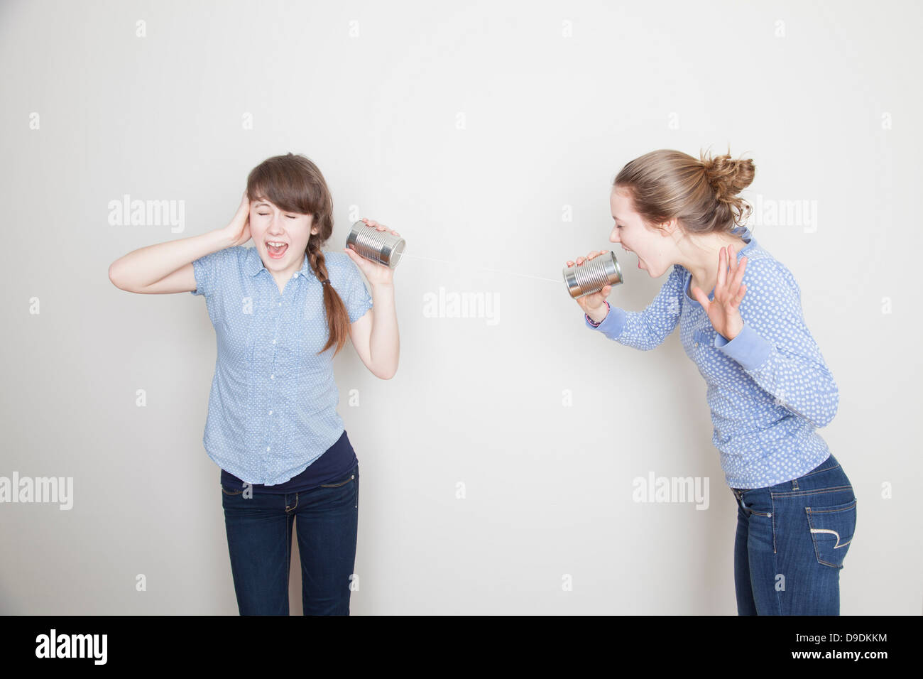 Two girls with tin cans, one shouting and one covering her ear - Stock Image
