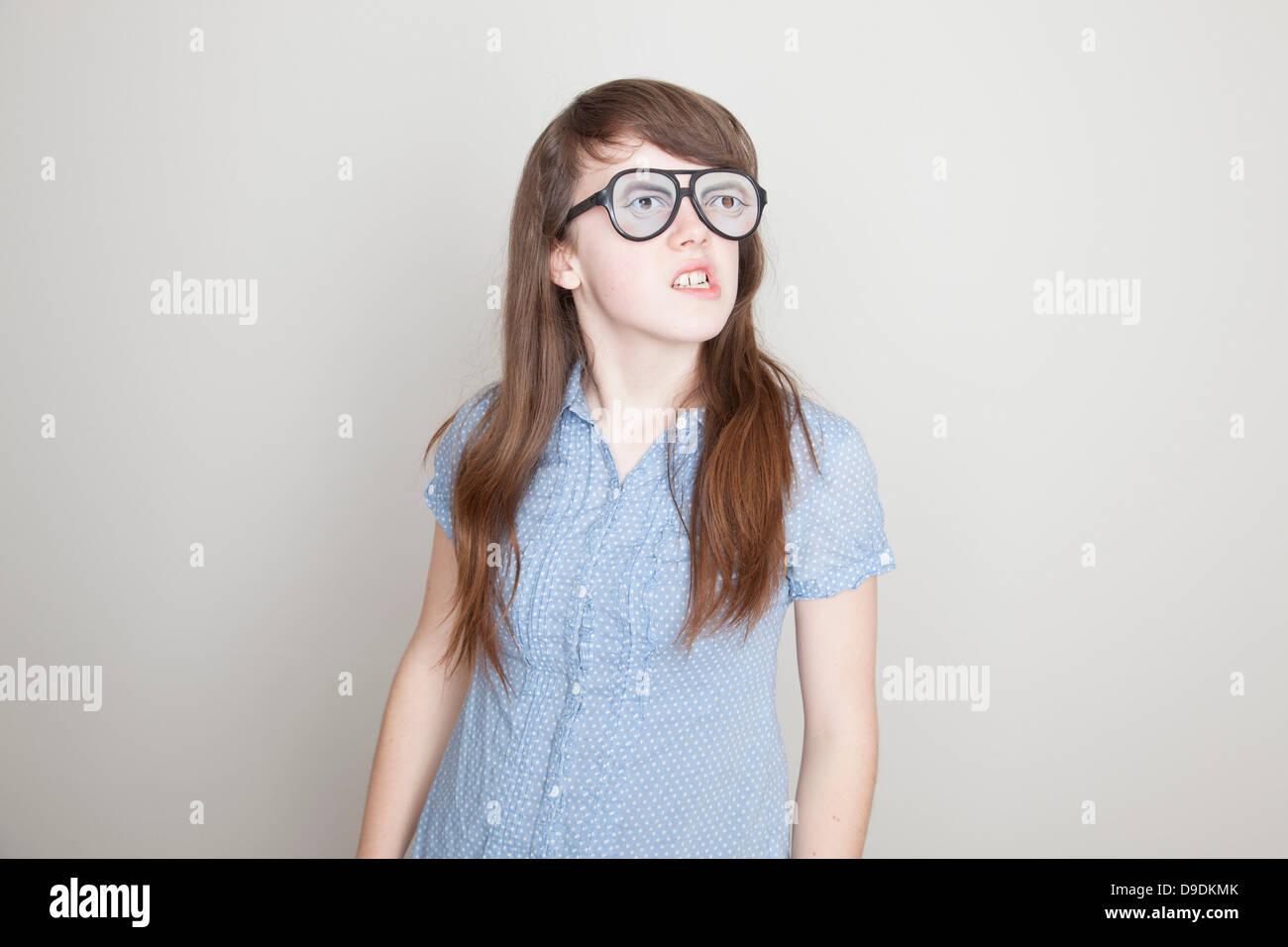 Girl wearing fake glasses grimacing Stock Photo