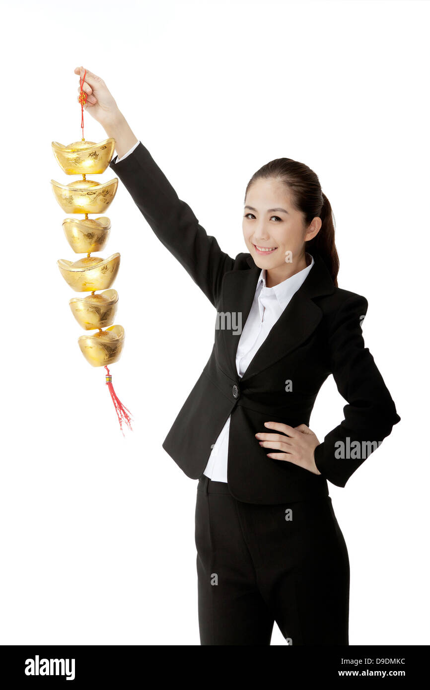 Business lady carrying a gold ingot - Stock Image