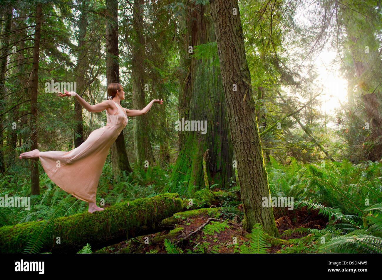 Mature woman standing on log in forest Stock Photo