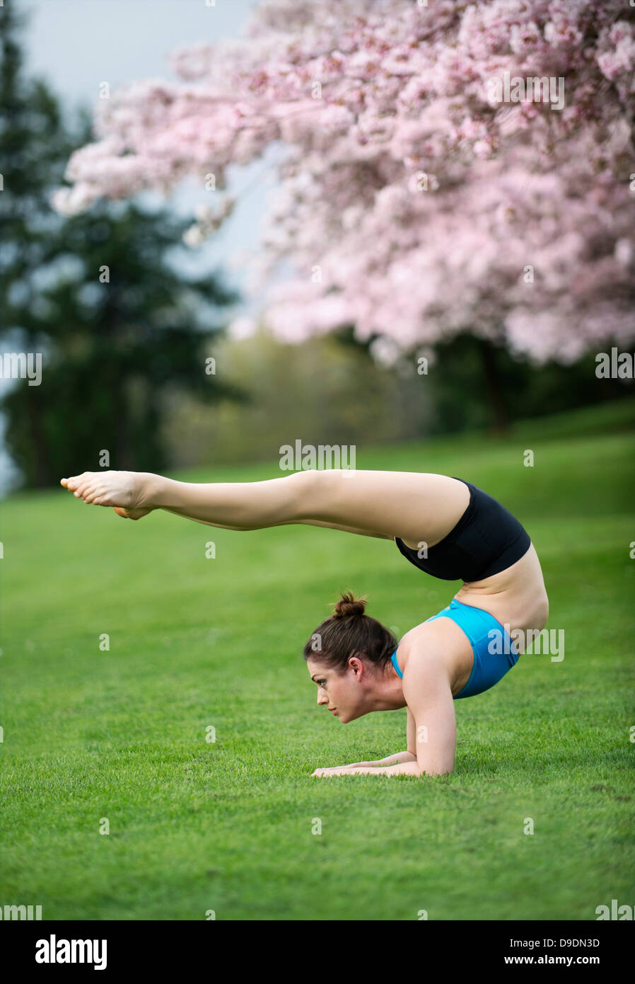 Acrobat performing stretches in park - Stock Image