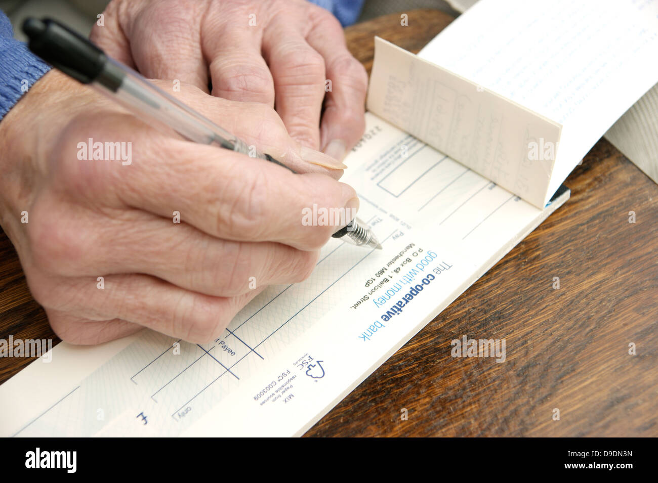 Elderly woman writing a cheque which is getting rarer these days (Co-operative bank cheque book) Co operative bank - Stock Image