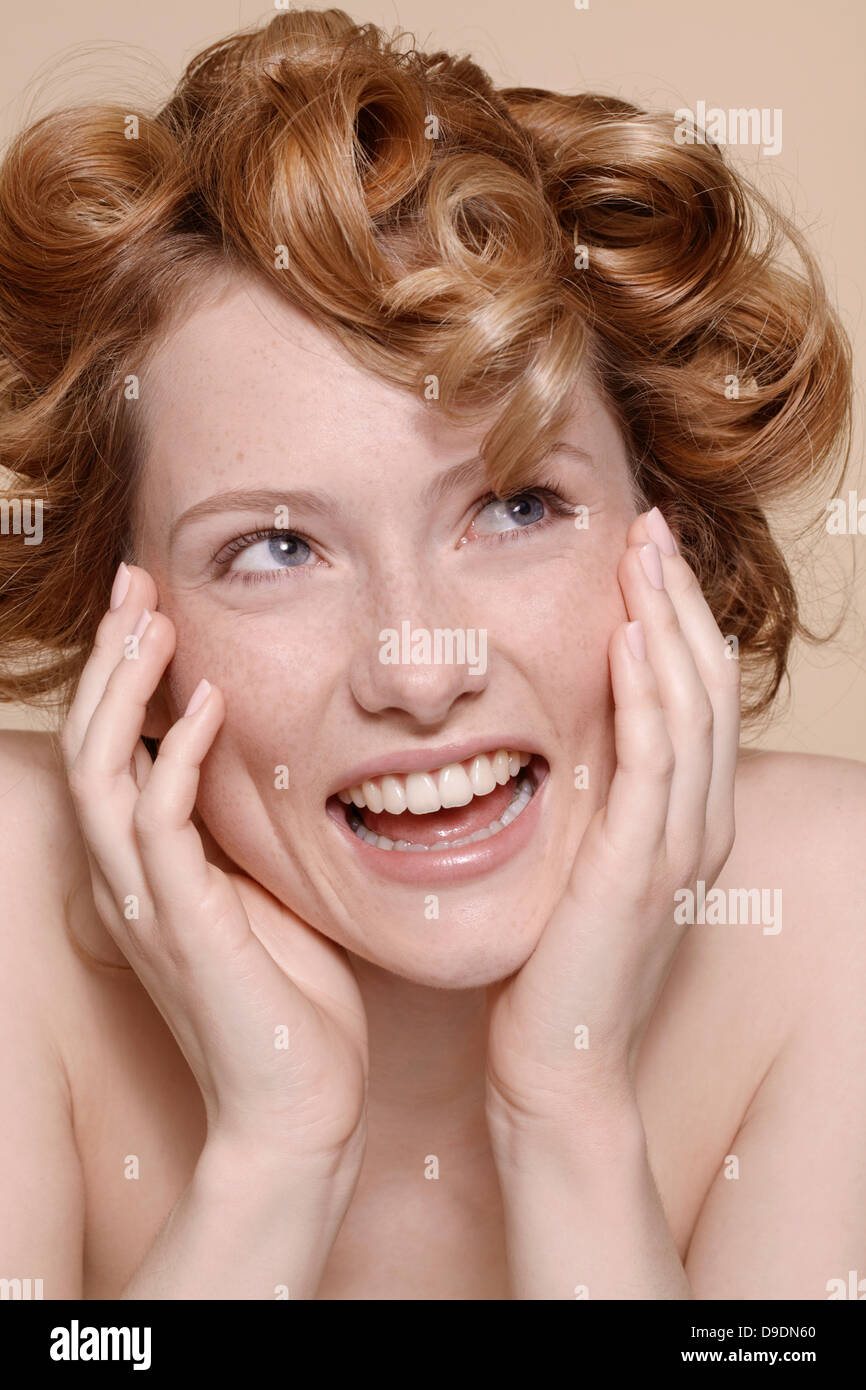 Young woman with curly red hair laughing - Stock Image