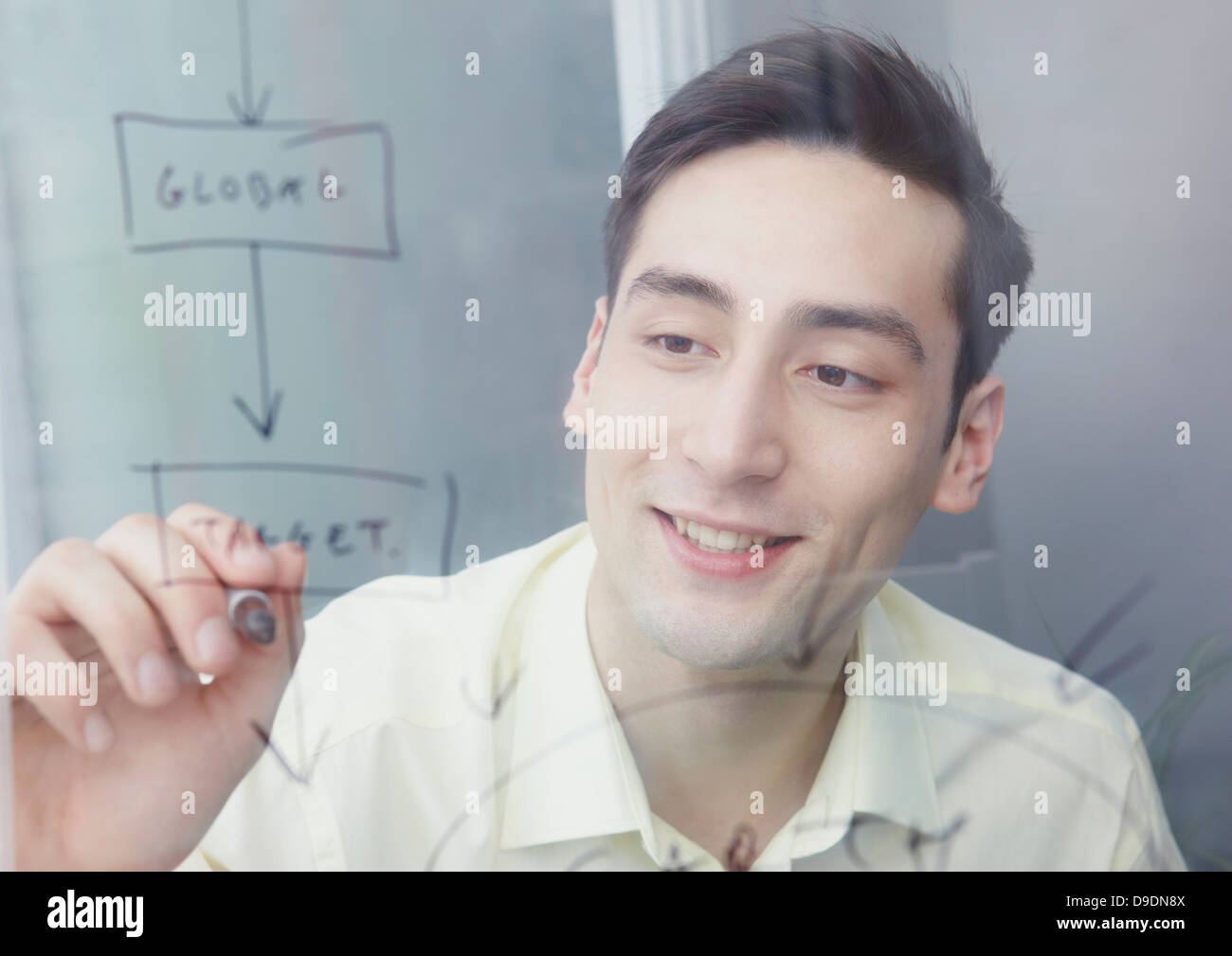 Man writing on glass with marker pen - Stock Image