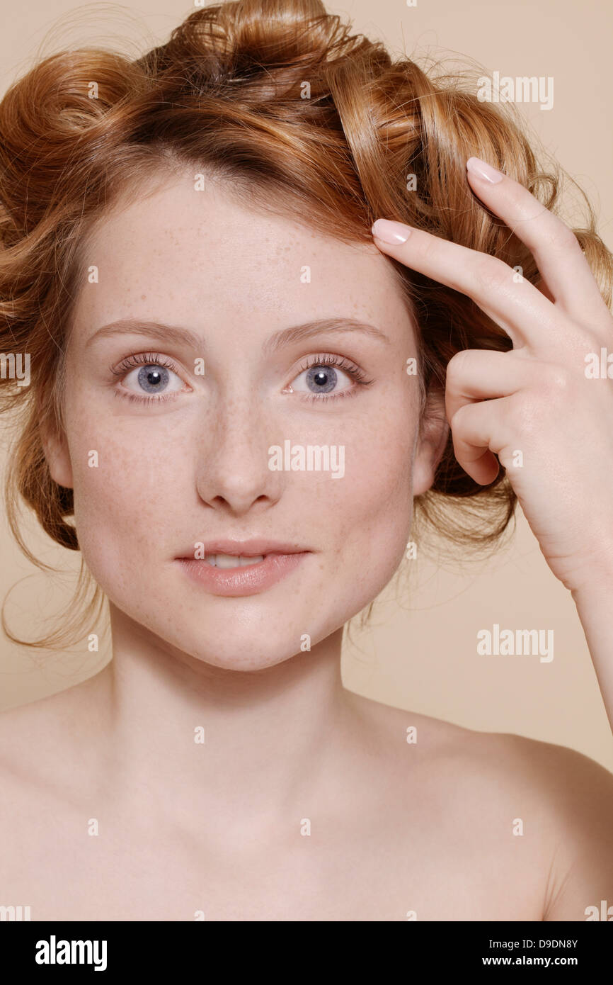 Young woman with curly red hair biting lip - Stock Image
