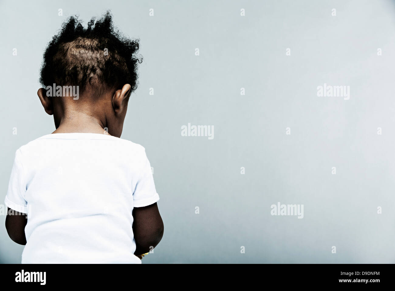Portrait of baby boy wearing white vest, rear view - Stock Image