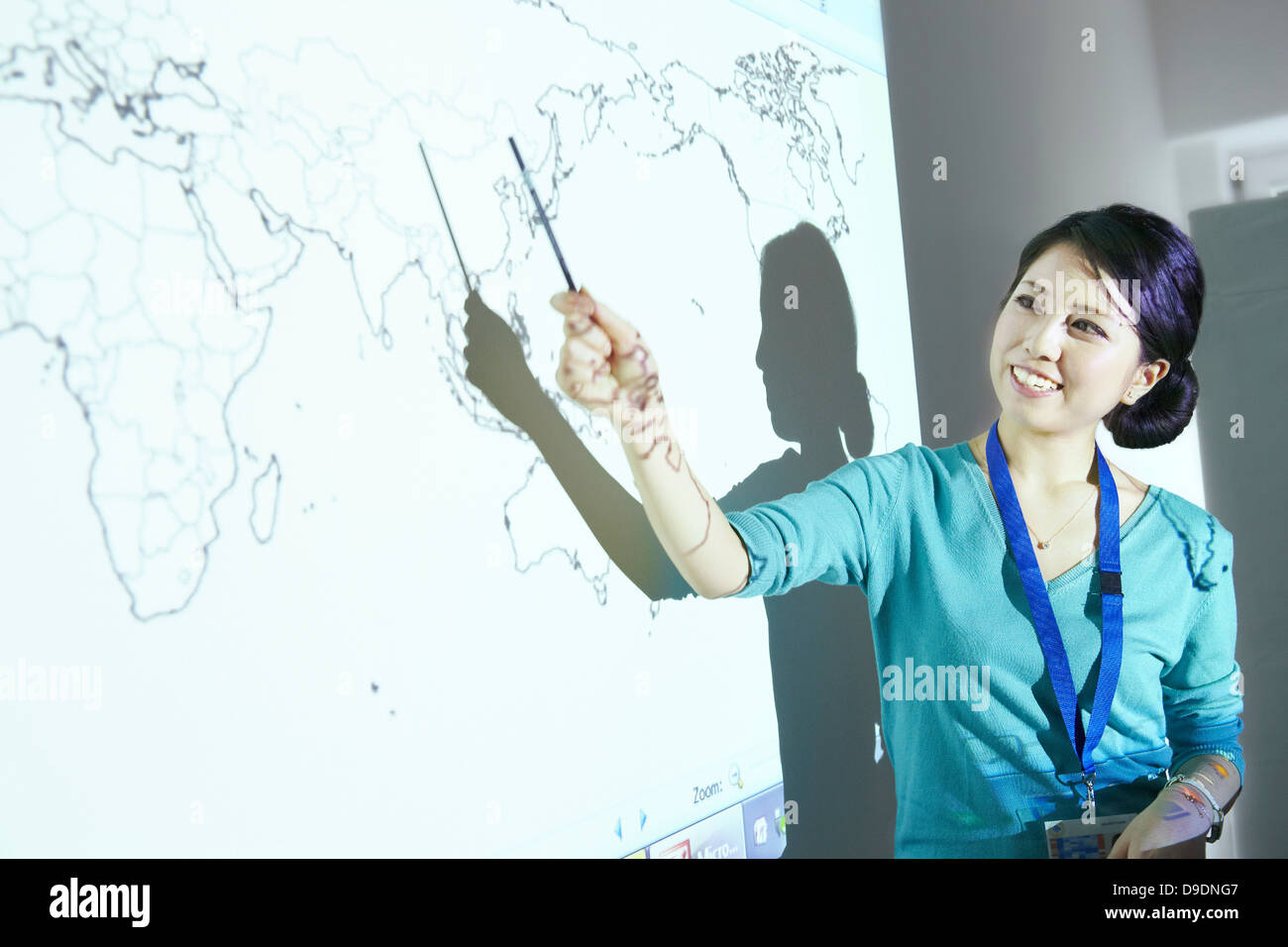 Woman doing presentation with world map projected on wall - Stock Image