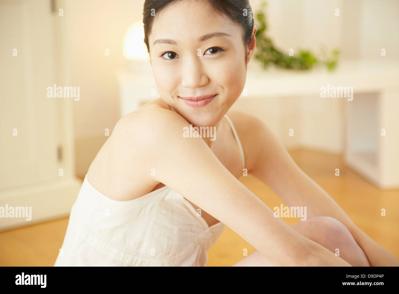 Portrait of woman wearing white vest looking at camera - Stock Image