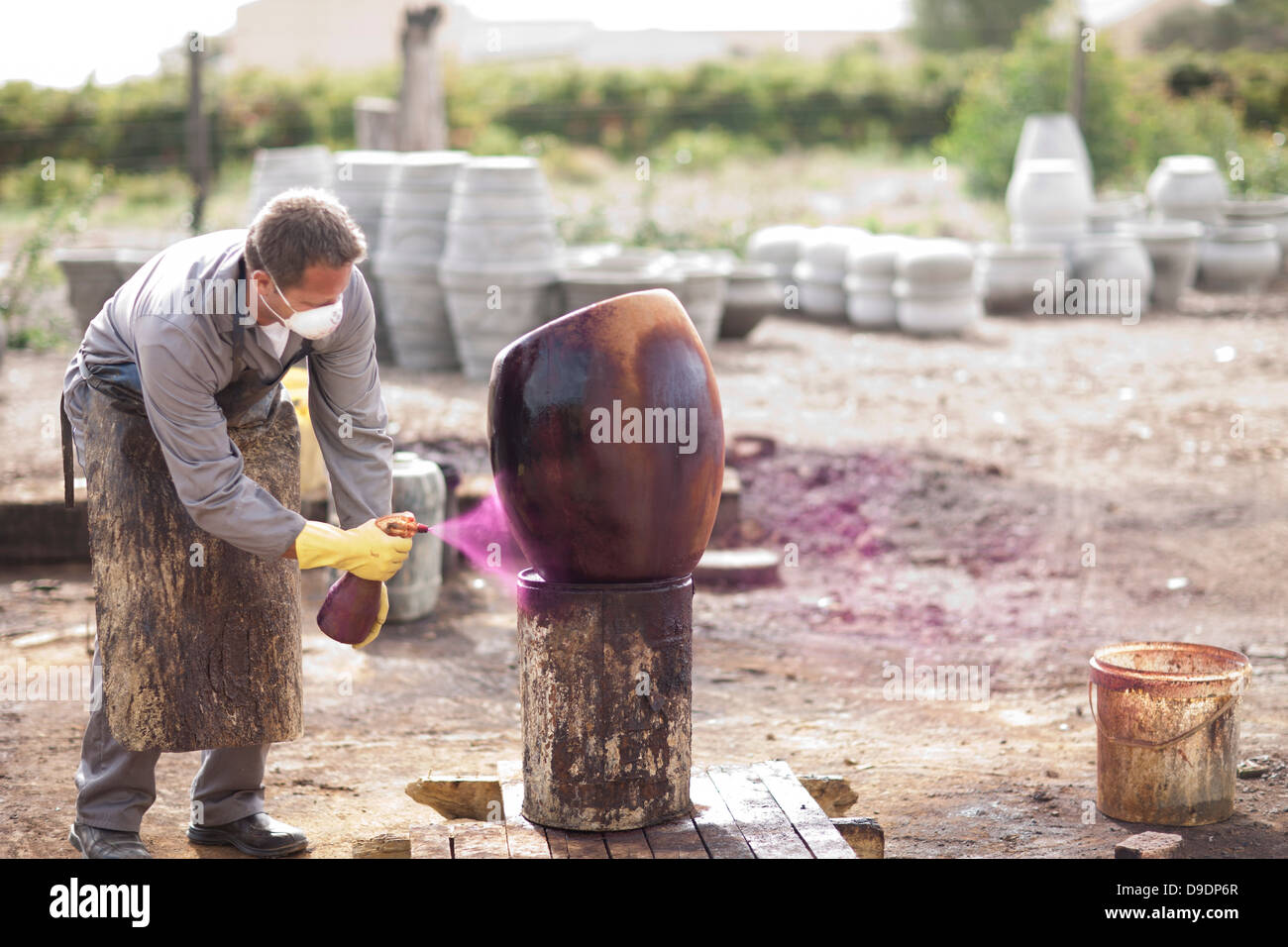 Spray painting a pot in the yard - Stock Image