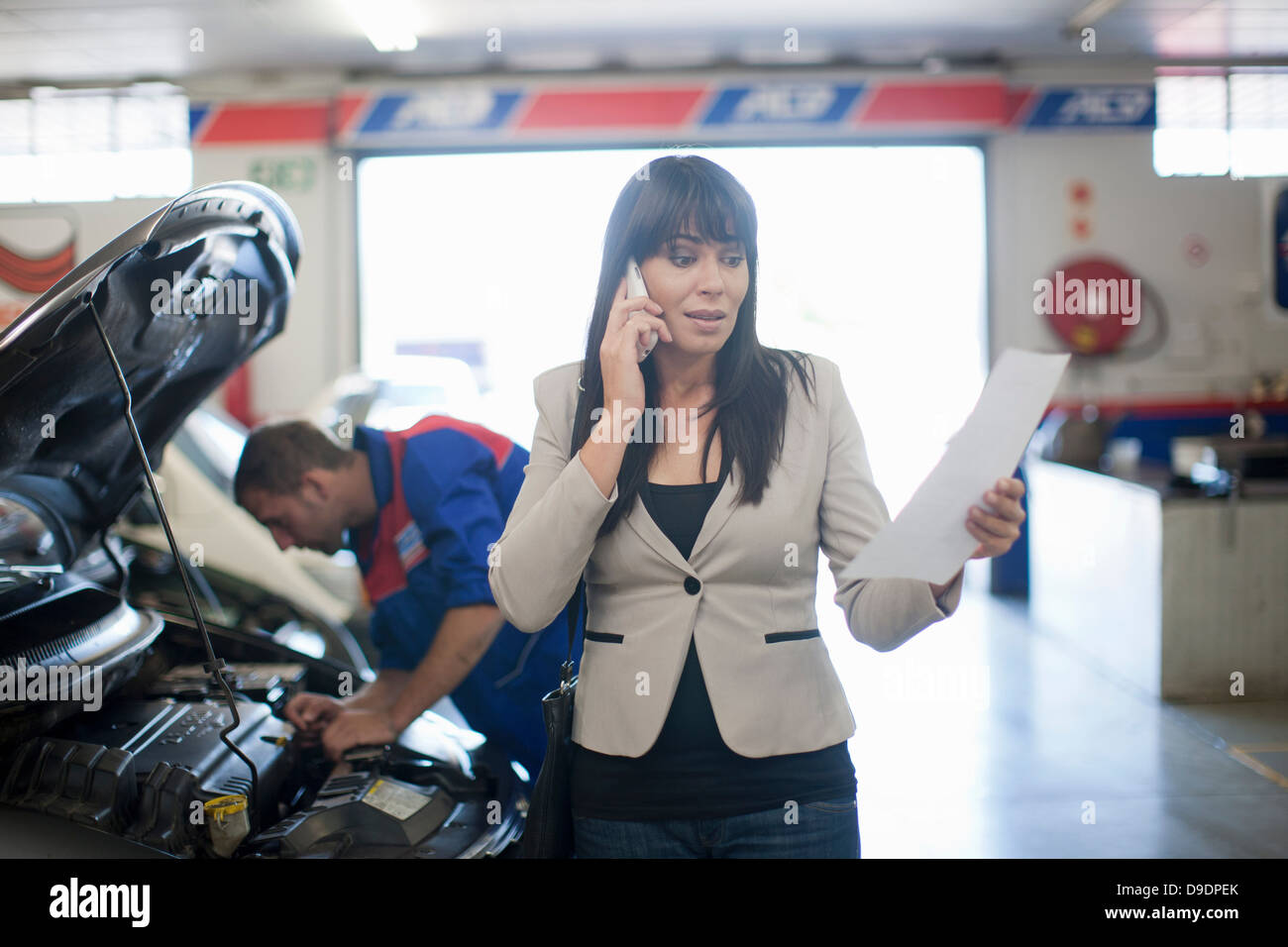 Woman unhappy reading document relating to her car - Stock Image