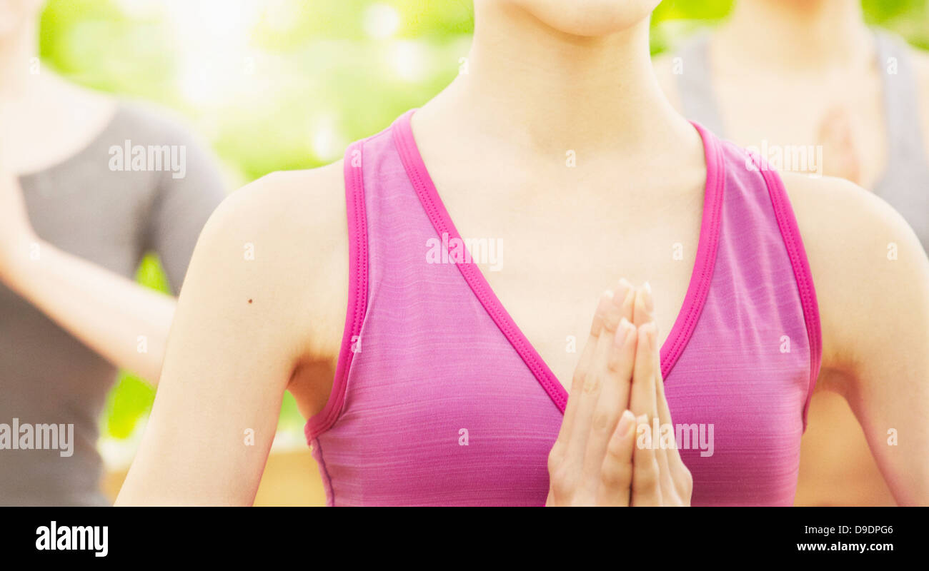 Woman wearing pink vest in prayer position, close up - Stock Image