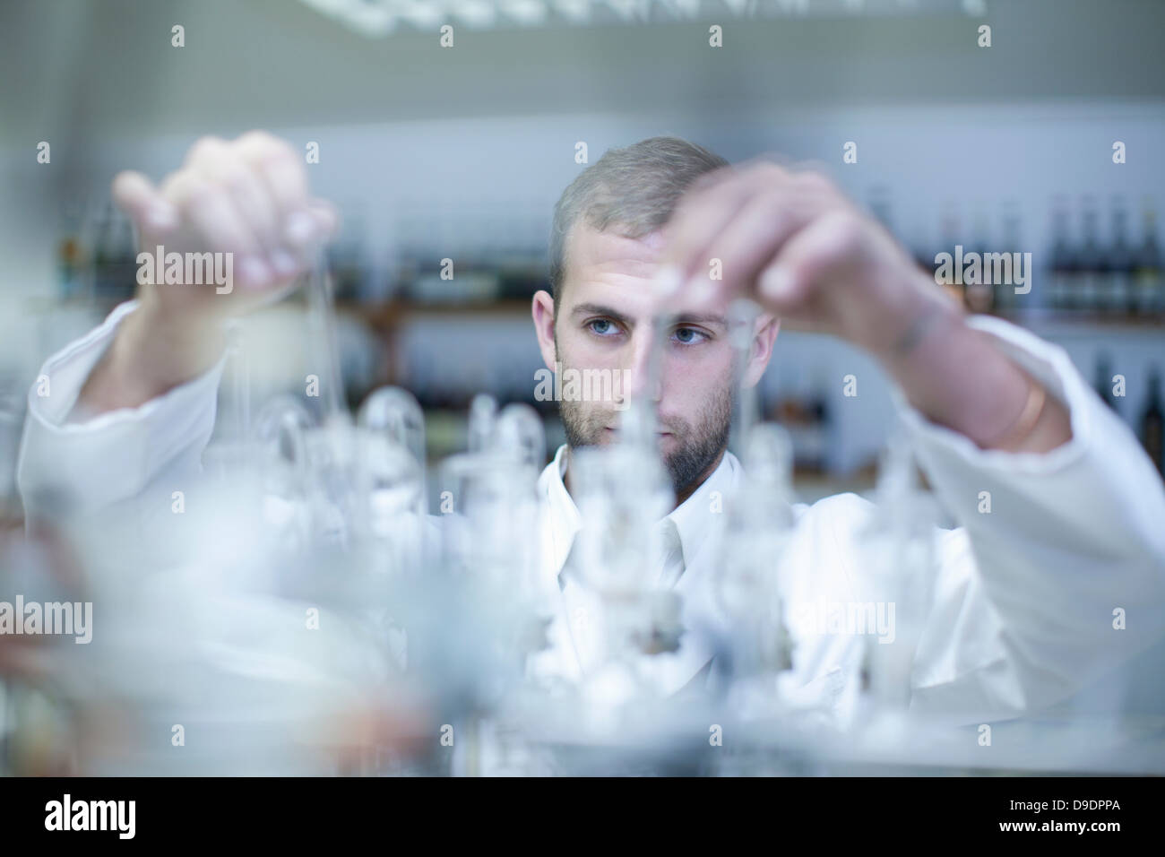 Oenologist mixing during sample testing in laboratory - Stock Image