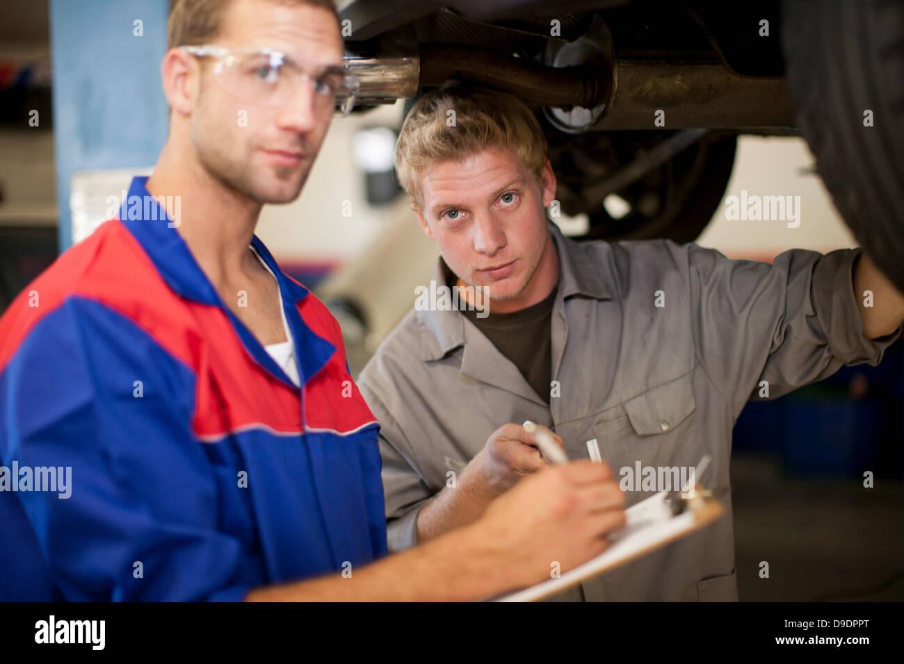 Car mechanics discussing and analyzing car repair - Stock Image