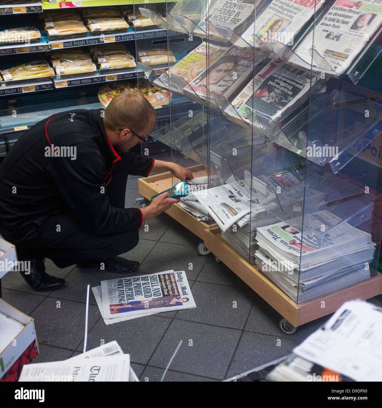 Delivery of daily UK newspapers being digitally scanned before going on sale at a branch of Spar convenience store - Stock Image