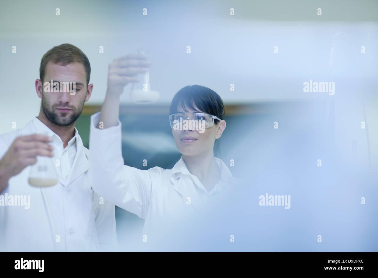 Laboratory technicians checking contents in laboratory beakers Stock Photo
